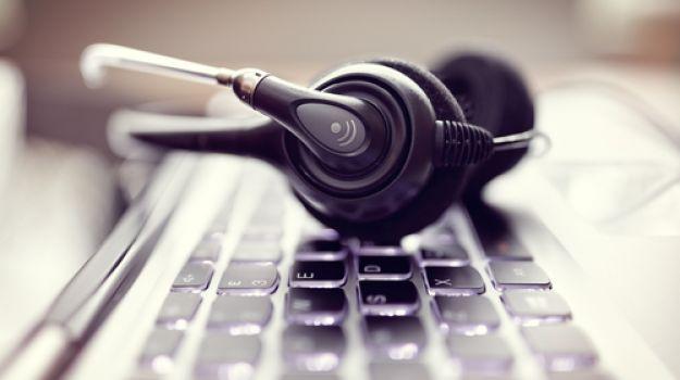 Fotografija prikazuje slušalke na računalniški tipkovnici.