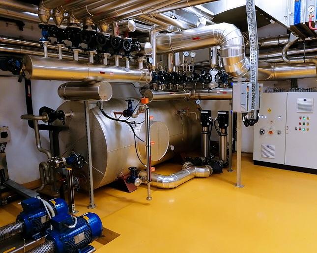 Fotografija prikazuje zbiralnik parnega kondenzata iz Novartisove proizvodnje trdnih in sterilnih izdelkov v Ljubljani. Kondenzat se s pomočjo črpalk vrača v toplovodno omrežje Energetike Ljubljana preko merilnega mesta za nadzor pretoka in prevodnosti.
